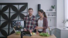 Strikt vegetarianbloggen, vloggers grabb och flickan förbereder sund mat med grönsaker och gräsplaner i kokkonst medan kamerasmar stock video