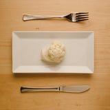 Strikt vegetarianlåg-carben bantar den rå blomkålen på den rektangulära plattan Royaltyfria Foton