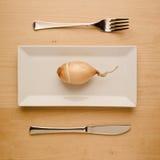 Strikt vegetarianlåg-carben bantar den rå löken på den rektangulära plattan Arkivfoton