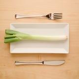 Strikt vegetarianlåg-carben bantar den rå oklippta vårlöken på den rektangulära plattan Arkivfoto