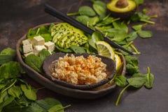 Strikt vegetarianlunch med råriers, avokadot och tofuen på en mörk backgrou Royaltyfria Bilder