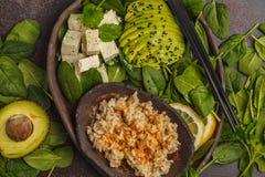 Strikt vegetarianlunch med råriers, avokadot och tofuen på en mörk bakgrund Arkivfoton