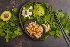 Strikt vegetarianlunch med råriers, avokadot och tofuen på en mörk bakgrund Royaltyfri Foto