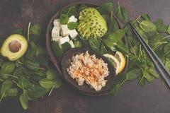 Strikt vegetarianlunch med råriers, avokadot och tofuen på en mörk bakgrund Arkivbilder