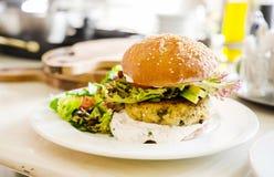 Strikt vegetarianquinoahamburgare i en restaurang Arkivbilder