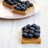 Strikt vegetarianrostade bröd med jordnötsmör, blåbär och chiafrö på en vit trätabell, sidosikt selektiv fokus för sund frukost arkivbilder