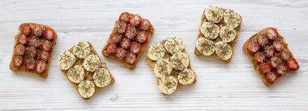 Strikt vegetarianrostade bröd med jordnötsmör, frukter och chiafrö på en vit trätabell, över huvudet sikt Sund frukost som bantar arkivbilder