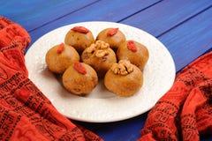 Strikt vegetariansötsaker med wallnuts och gojibär på orange etniska clo Royaltyfri Bild