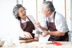 Strilar skrattar höga par för lycklig familj degen med mjöl och medan baka hemmastatt kök för kakor Baka och royaltyfri foto