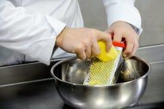 Strimla potatisar på ett rivjärn Royaltyfri Bild