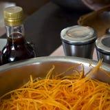 Strimlade morötter i en yrkesmässig stor stålpanna Sås och sp Royaltyfria Foton