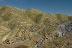 Strimmiga gräsplan- och regnbågeberg i den Maragua krater Bolivia med lantgårdhus royaltyfri bild