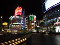 Strimmor för en buss förbi Tokyo neontecken Arkivfoto