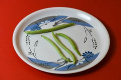 String beans on plate close on isolated red background stock image