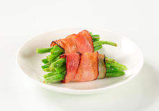 String beans wrapped in bacon. String beans wrapped in slices of bacon Royalty Free Stock Image