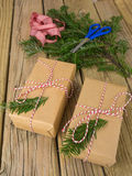 String and brown paper parcels with conifer decoration, check ri Stock Image