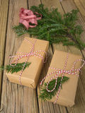 String and brown paper parcels with conifer decoration and check Stock Image