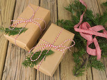 String and brown paper parcels with conifer decoration and check Royalty Free Stock Image