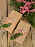 String and brown paper parcels with conifer decoration and ribbo Stock Photos
