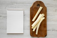 String cheese on rustic wooden board, blank notepad over white wooden background, top view. Healthy snack. From above, overhead, stock images
