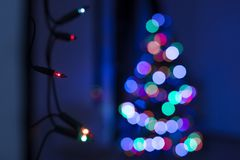 String of Christmas lights hanging on the wall, with defocused xmas tree in the background. Christmas lights bokeh. String of Christmas lights hanging on the royalty free stock photography