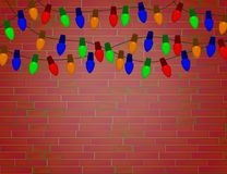 String of Color christmas light bulbs on red brick wall. Royalty Free Stock Image