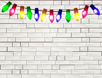 String of Color christmas light bulbs  on white brick background Royalty Free Stock Photos