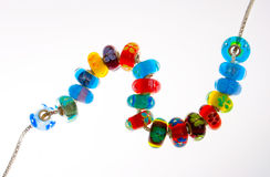 String of glass beads. Colorful handmade glass beads strung through a silver chain or necklace Stock Photography