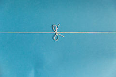 String knot over blue cardboard. Blue cardboard sheet with white string tied in a knot Royalty Free Stock Photography