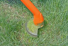 String lawn trimmer mower cutting grass, over a grass background. Close up of string lawn trimmer mower cutting grass, over a grass background Royalty Free Stock Photo