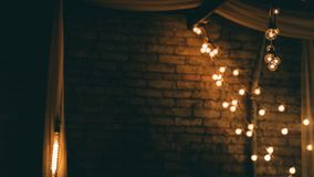 String of lights next to a brick wall. A string of vintage lights hanging near a brick wall stock photography