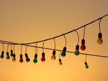 String of Multicoloured Light Bulbs at Sunset Stock Photography