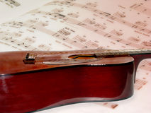 String music and notes. Side view of acoustical guitar resting on an opened page of sheet music Royalty Free Stock Image