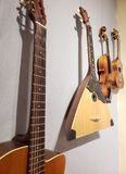 String musical instruments on a wall. Acoustic guitar, balalaika, violin and ukelele hanging on a wall Stock Images