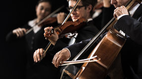 String orchestra performance. String orchestra performing on stage with cello on foreground stock photos