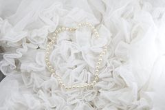 String of pearls. Pearl necklace with white ruffles in the background stock photography