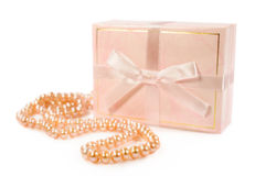 String of pearls and a pink gift box Royalty Free Stock Photo