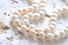Pearls on stone. A string of pearls on a stone background Royalty Free Stock Photography