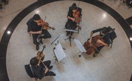 A string quartet, playing at Bangkok Art and Cultural center. BANGKOK, THAILAND - January 30, 2017: A string quartet, play classical music, at the Bangkok Art Stock Image