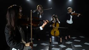 String quartet playing in a dark room on the floor are scattered sheets with notes. Black background. String quartet playing in a dark room with lanterns on the stock video