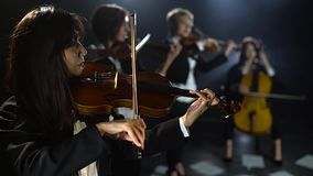 String quartet playing in a room on the floor are scattered sheets with notes. Black background. String quartet playing in a dark room with lanterns on the floor stock footage
