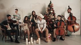 34b87687a9d21 String quintet with vocalist perform song in room with christmas scenery stock  footage