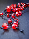 String of red beads. String of red beads on black background Royalty Free Stock Photo