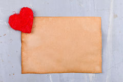 String red heart near old paper Stock Images