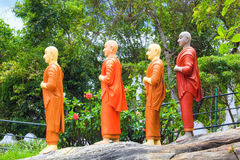 A string of statues of Buddhist monks in orange tones in a Buddhist temple in Sri Lanka Stock Photos