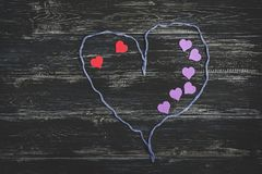 A string of threads on a black wooden background, inside are red and lilac hearts. Valentine`s Day. Royalty Free Stock Photo