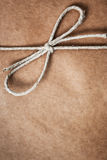 String tied in a bow, over brown package paper Royalty Free Stock Photo