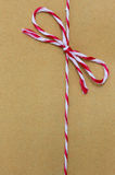 String tied in a bow, over brown paper Royalty Free Stock Image