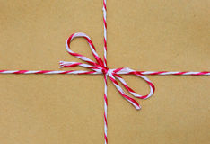 String tied in a bow, over brown paper Stock Photography
