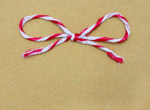 String tied in a bow, over brown paper Royalty Free Stock Photography